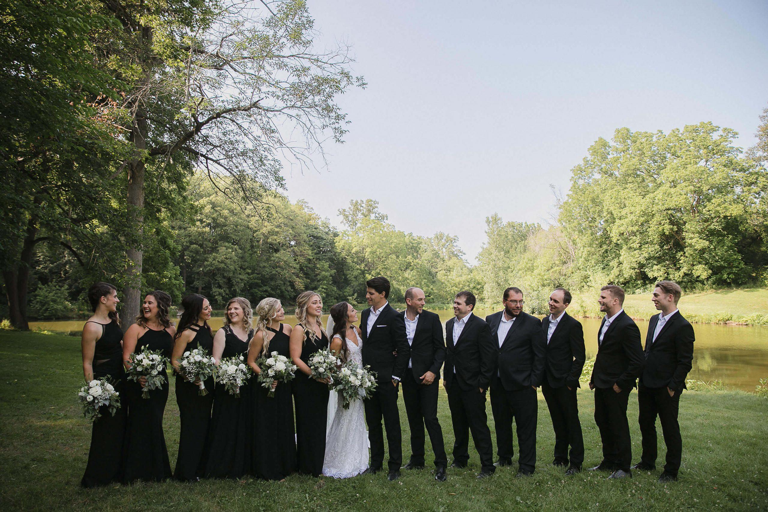 Wedding photo bridal party pond public park, all black wedding, black bridesmaid dresses, white and green bouquets