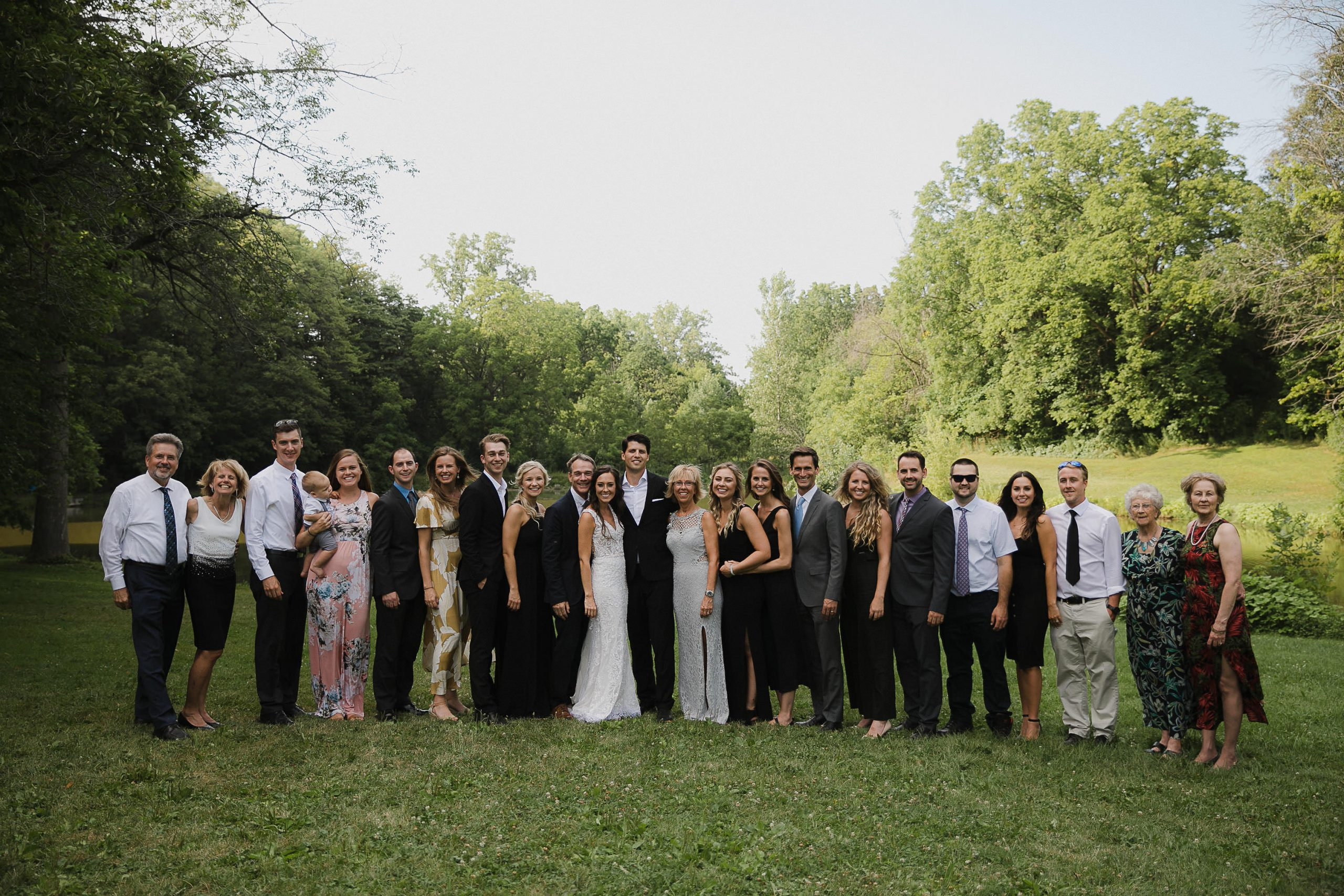 Wedding photo family photos in front of a pond, harsh light full daylight, big group photos