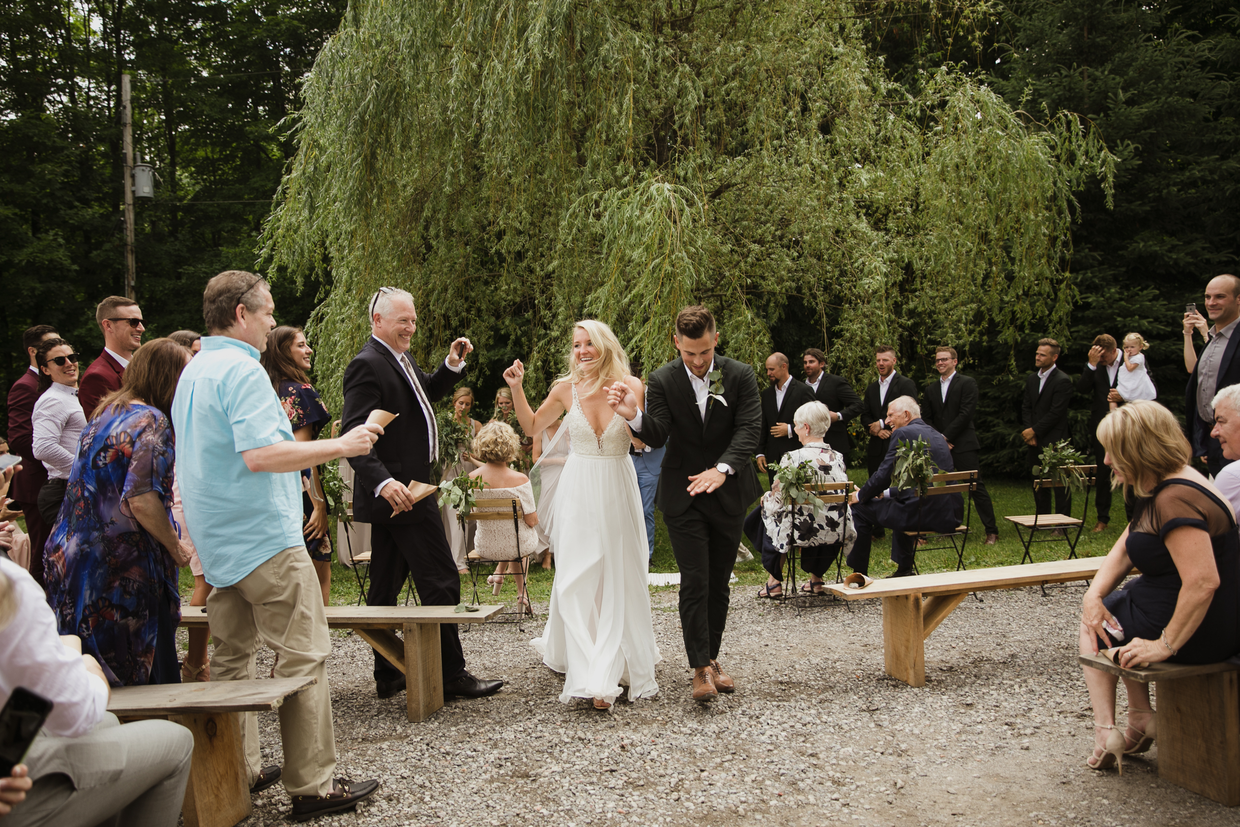 Wedding photo ceremony bride and groom celebrating down the aisle eucalyptus thrown at them by guests