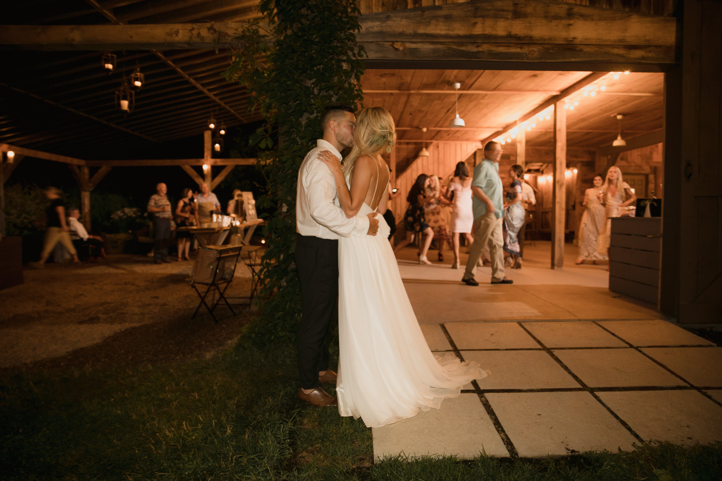 Wedding photo bride and groom reception candid kiss outside dance floor