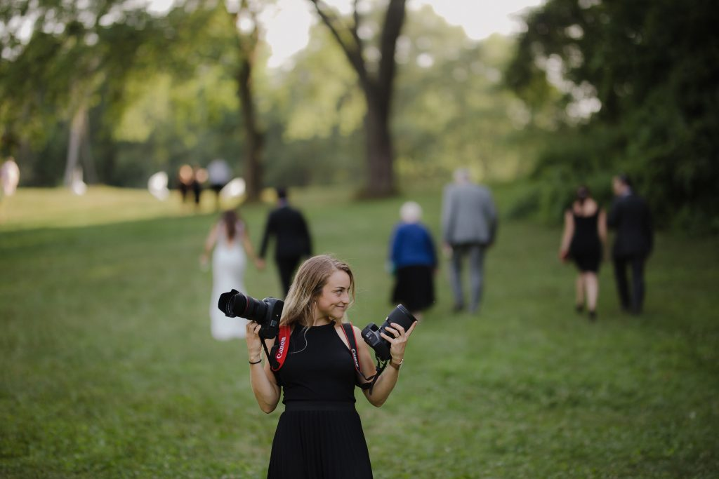 Wedding photo documentary style wedding photographer candid holding two cameras