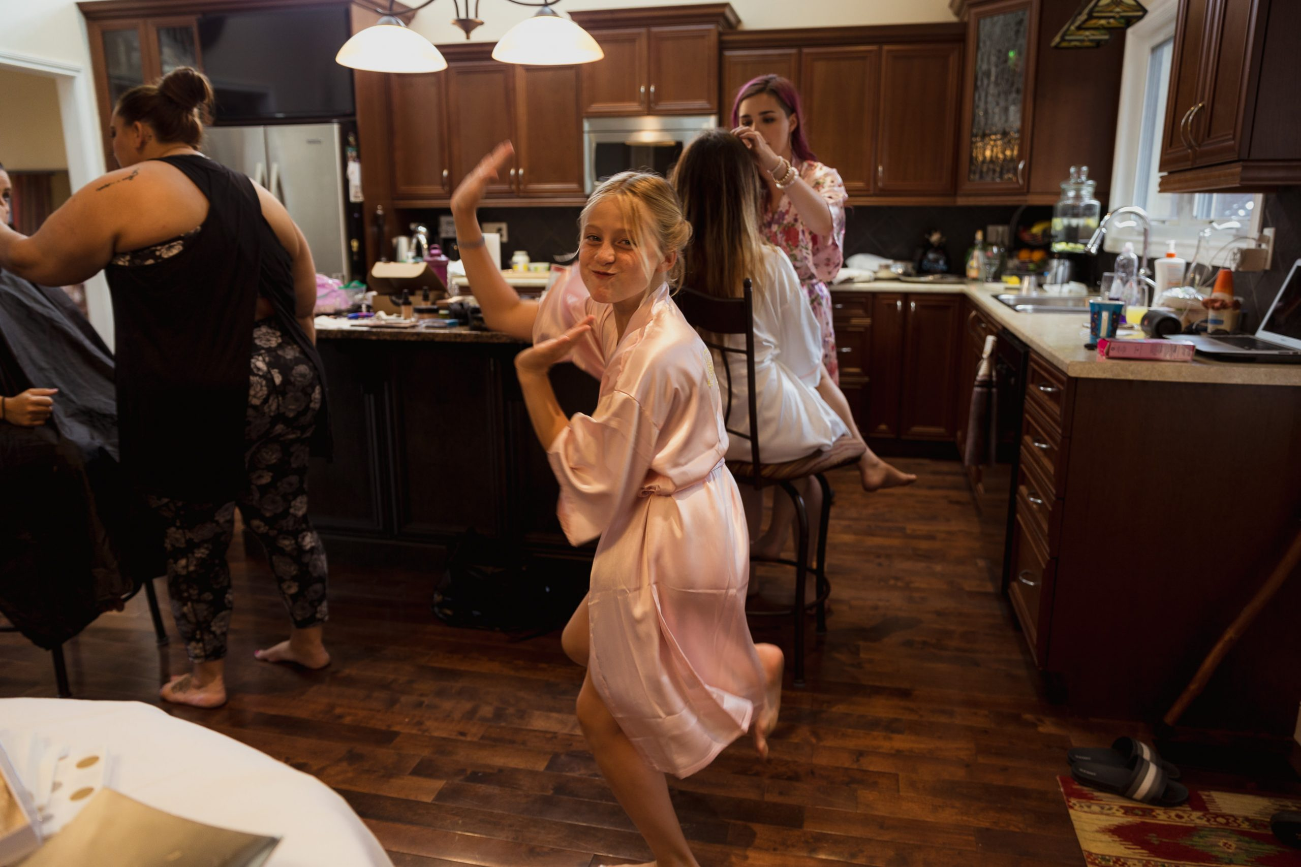 Wedding photos girls getting ready flower girl dancing in the kitchen in her bridesmaid robe