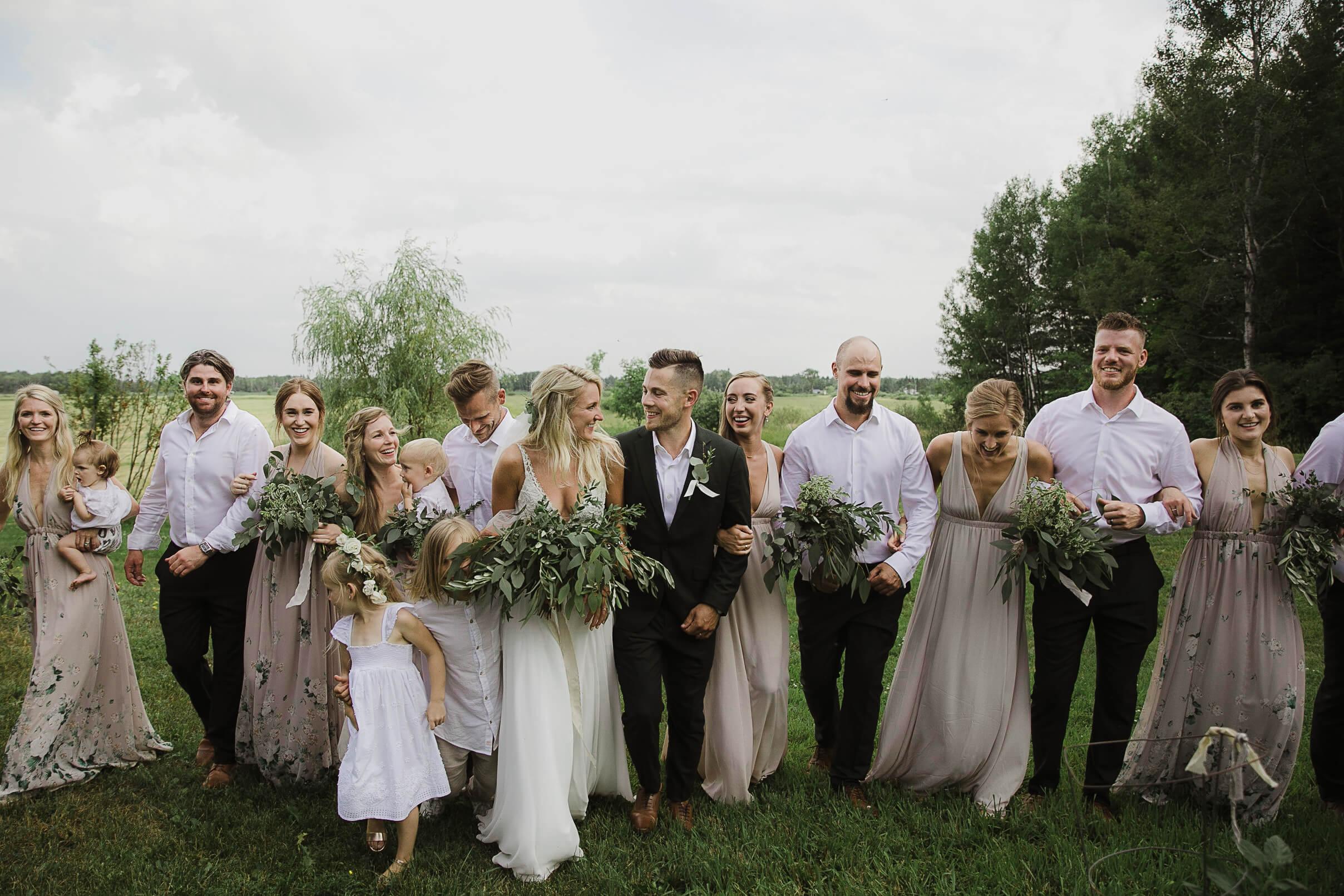 Wedding photo bridal party walking eucalyptus bouquets neutral tones bridesmaid dresses