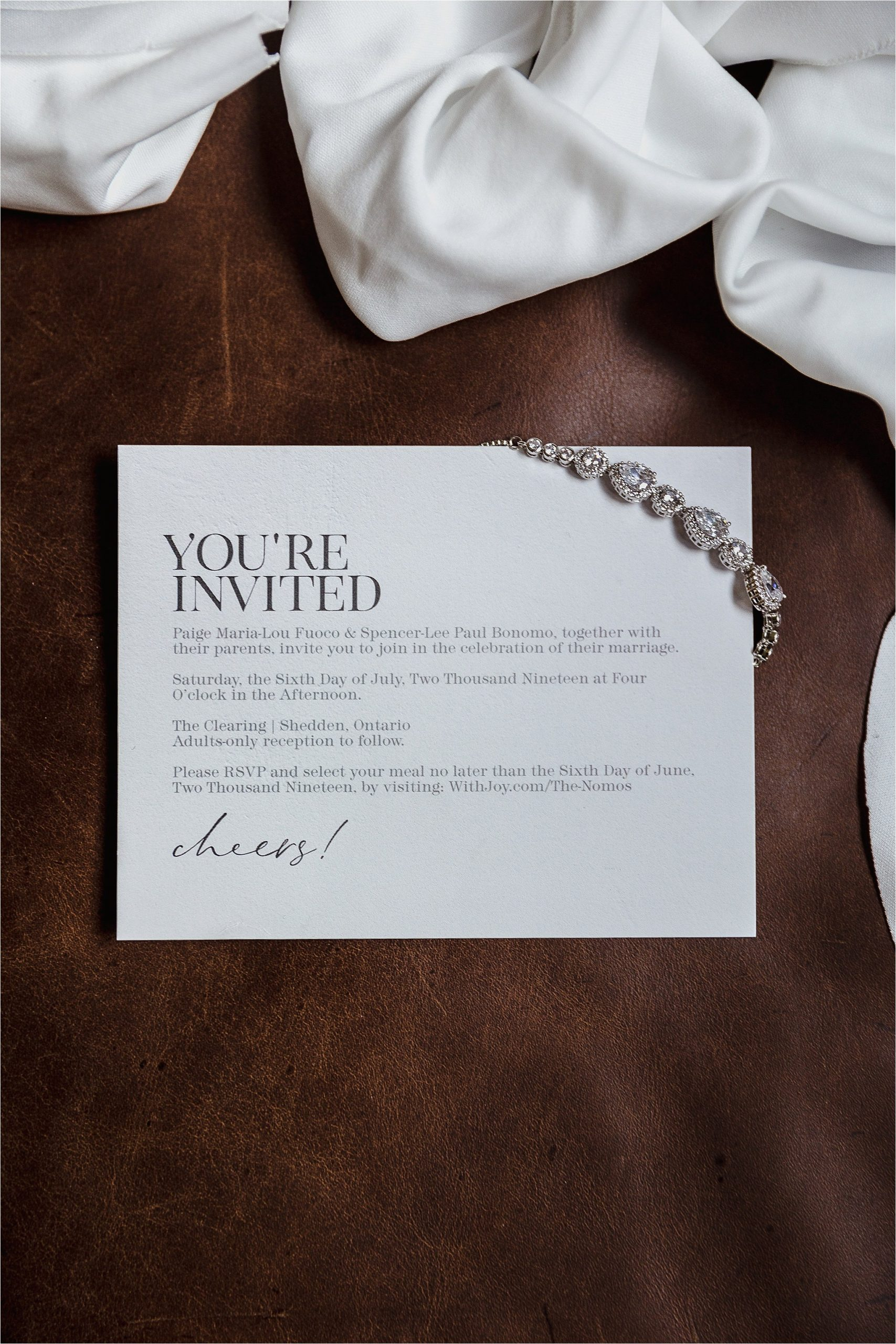 Wedding invitation and bride's bracelet on leather couch