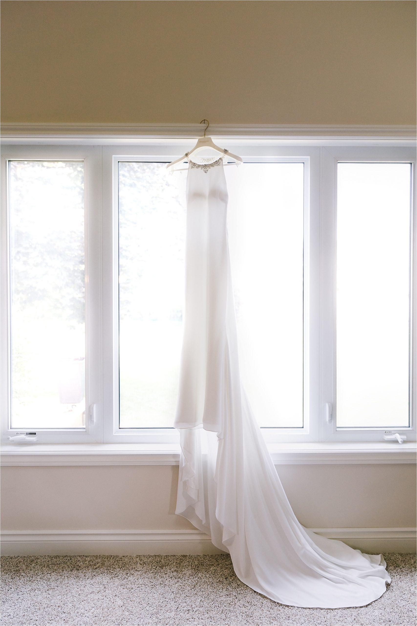 Bridal gown wedding dress from Provonias hanging in front of window
