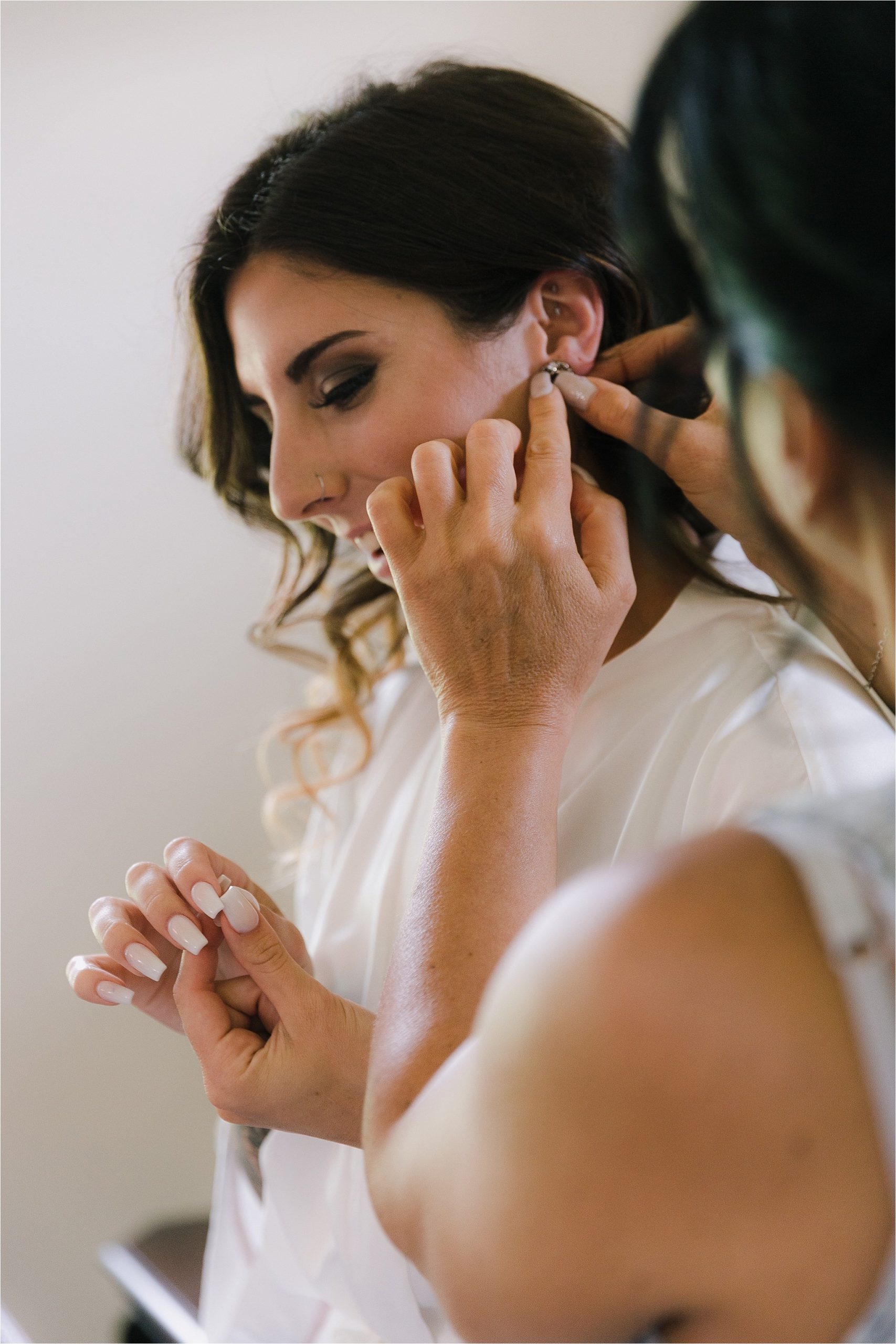 Mother of the bride putting in earrings for bride