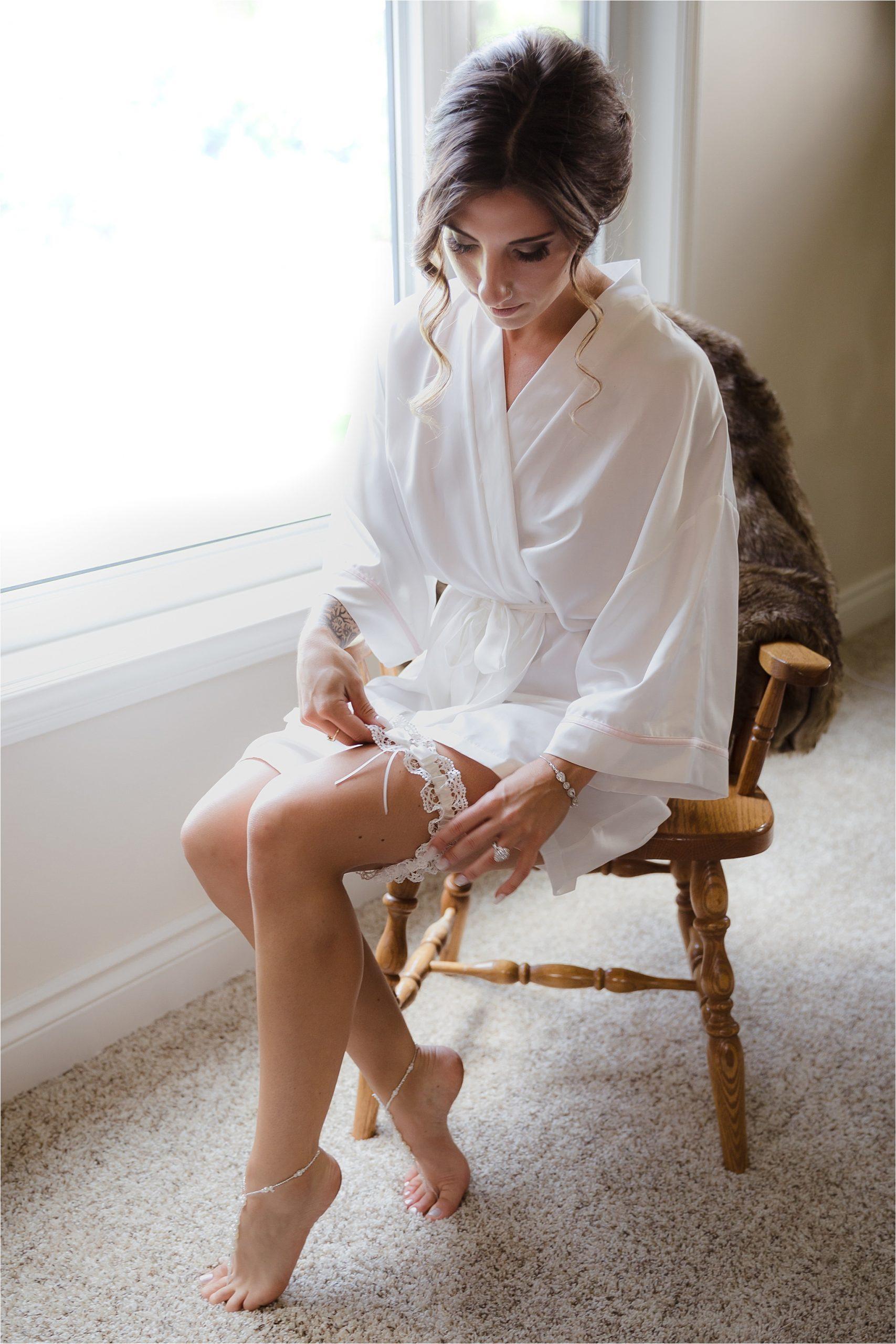 Bride sitting in wedding robe putting on garder