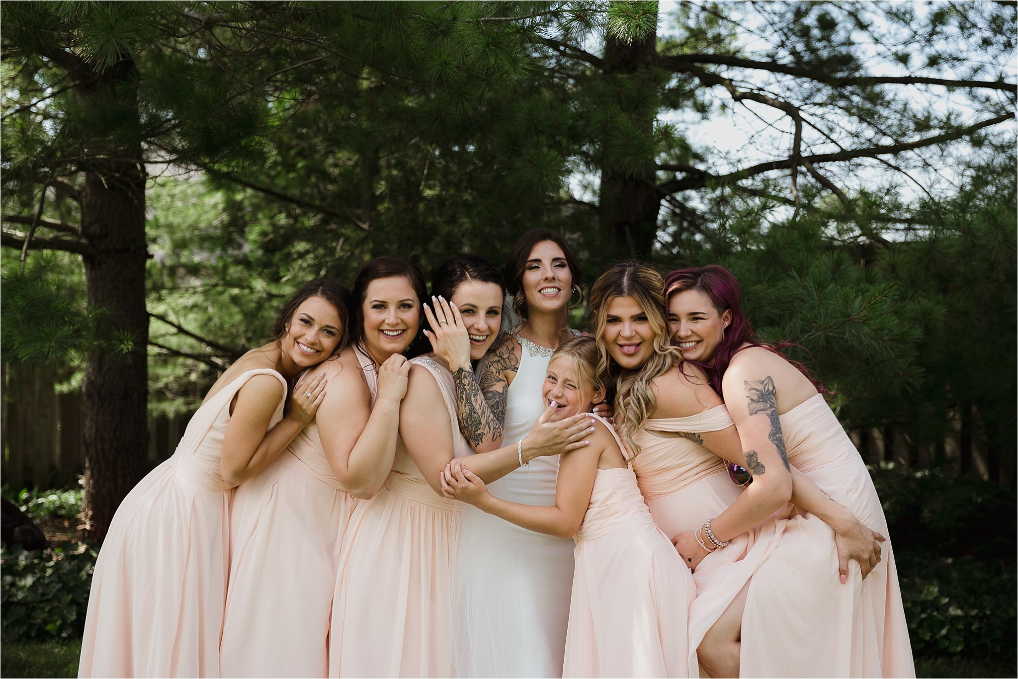 Bride with bridesmaids outside in long blush dresses