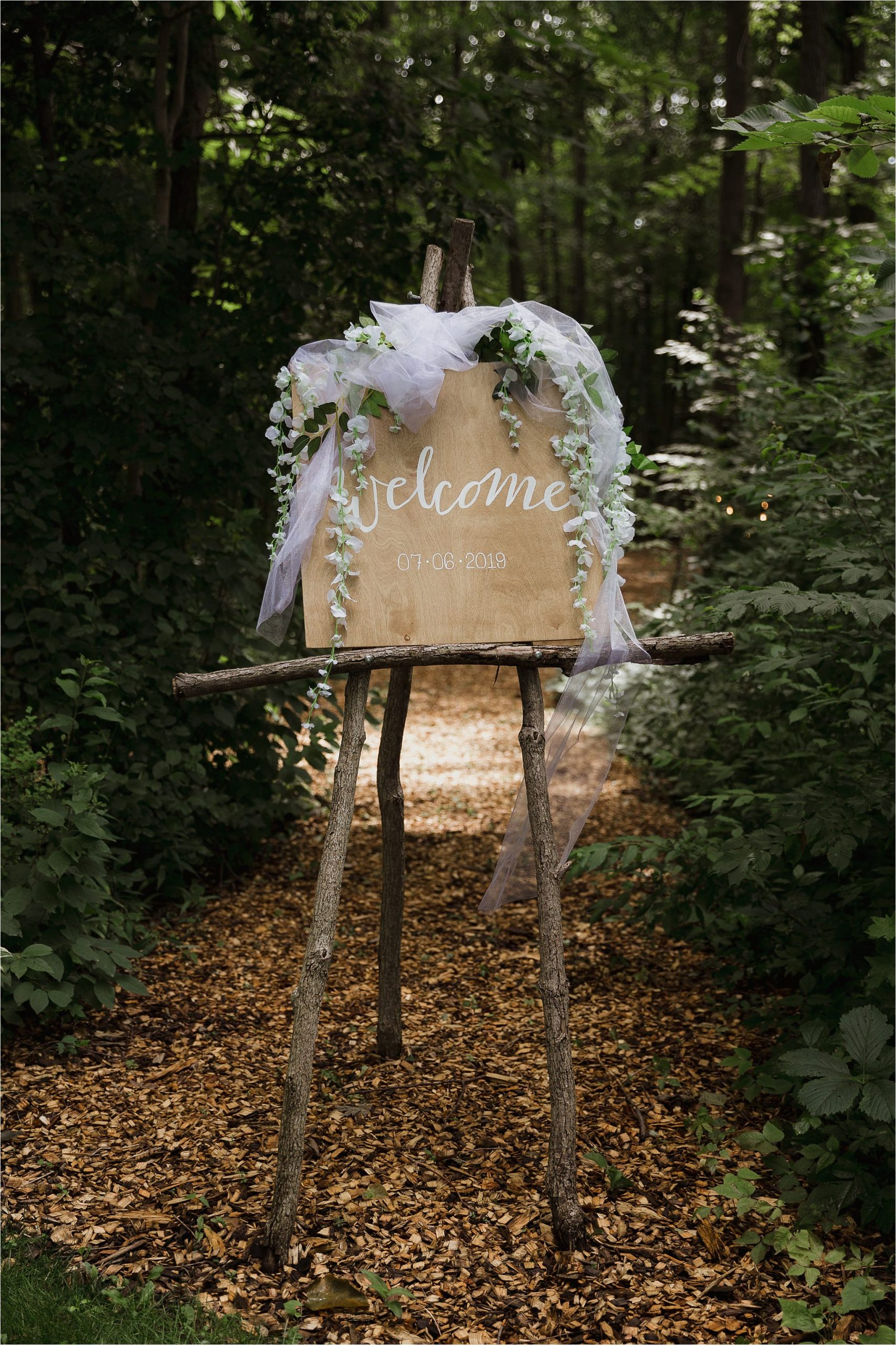 The Clearing wedding venue welcome ceremony sign green floral and tulle