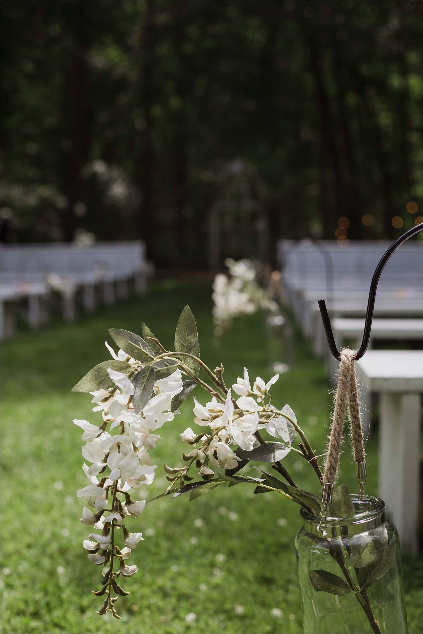 The Clearing wedding venue ceremony decoration with benches and floral mason jar arrangements