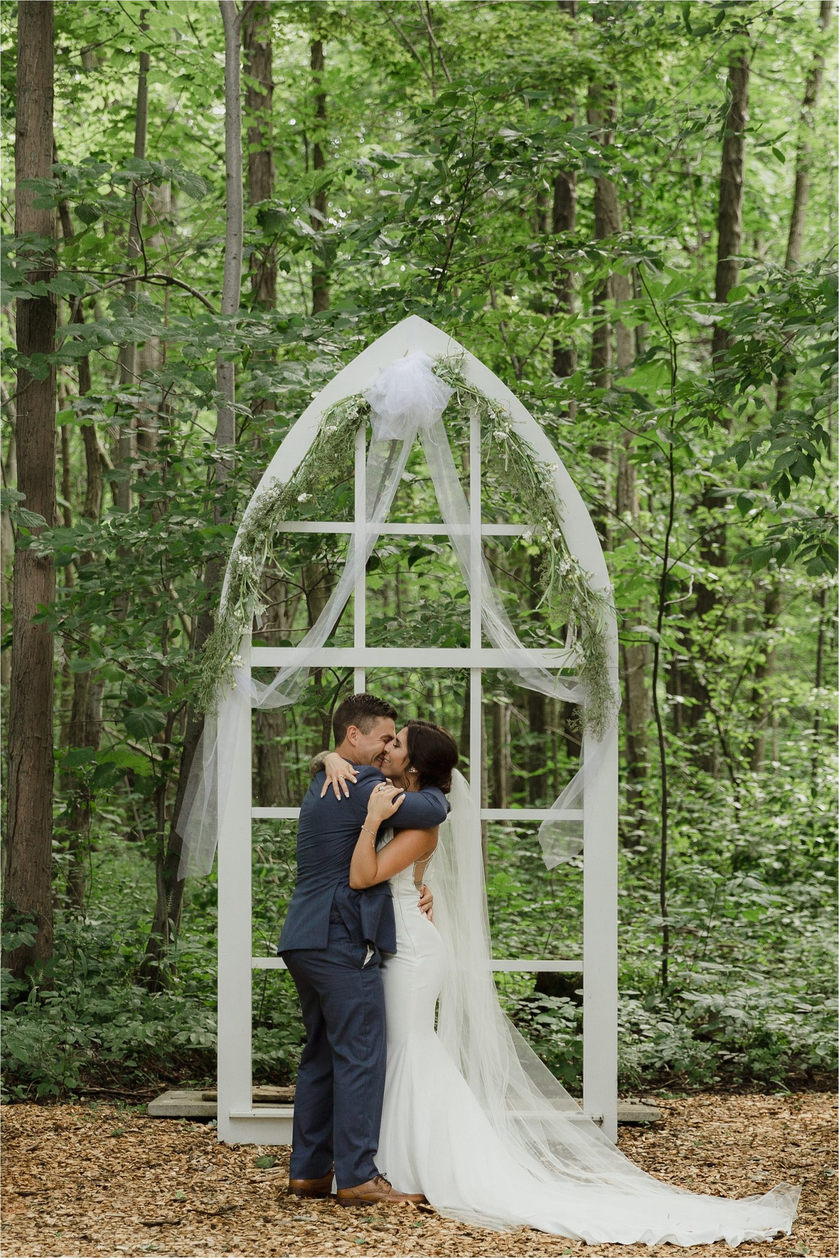The Clearing ceremony wedding venue bride and groom first kiss in front of arbor