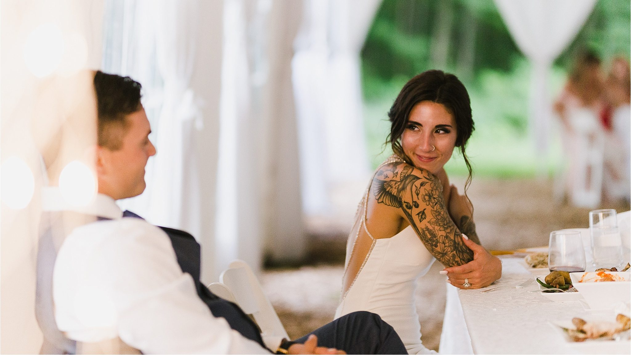 Bride and groom candid moment at outdoor tented wedding reception