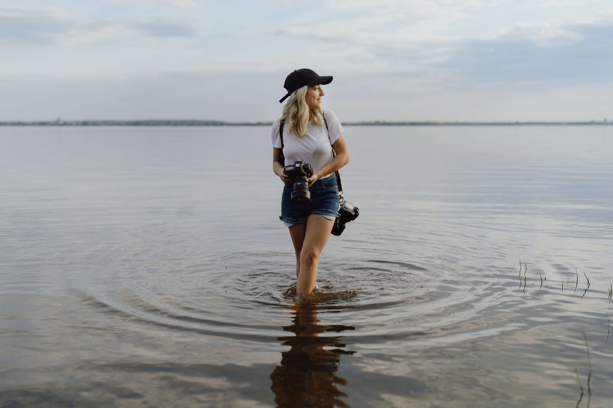 Sonia holding camera in water Sonia V Photo -Documentary Style Candid Photographer - Ottawa Ontario Kemptville Destination Photographer - Authentic Colour Photography - Wedding Photographer - Branding Photographer - Small Business Headshots - Engagement Photos - Family Portraits - Lifestyle